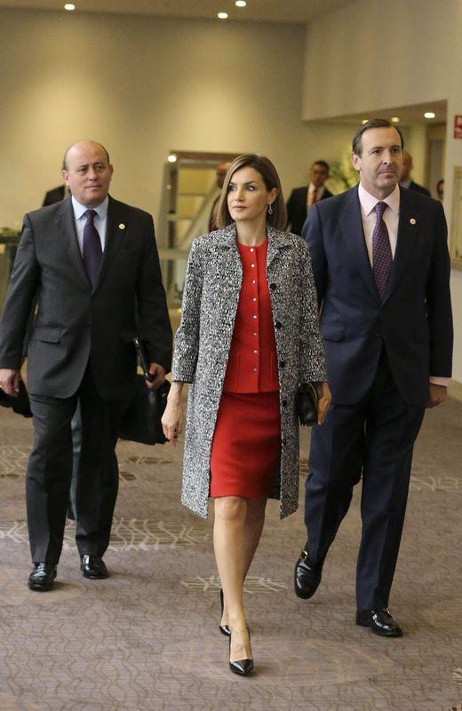 Letizia optó por un traje rojo de falda con cuerpo abotonado, al que sumó un abrigo en blanco y negro de manga tres cuartos, cartera de Nina Ricci y stilettos, todo en negro - 1024x