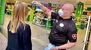 Un empleado de seguridad toma la temperatura a un cliente en el supermercado