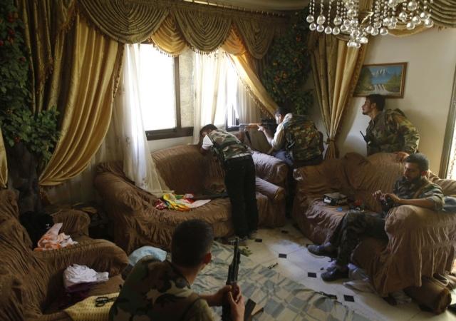 Un soldado del ejercito libre de Siria dispara su rifle de francotirador desde una casa en Aleppo. 14 de Agosto de 2012. Reuters -