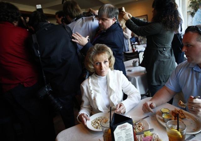 Una mujer come sopa de pescado mientras los medios de comunicación y seguidores rodean el candidato presidencial republicano Rick Santorum en un acto de campaña en un restaurante.  Florence, Carolina del Sur, 15 de enero de 2012. Reuters -
