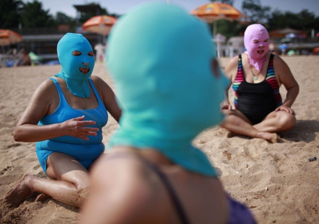 Mujeres chinas usan máscaras de nylon para bloquear los rayos de sol en su visita a una playa de Qingdao, provincia de Shandong. 6 de julio 2012. Reuters -