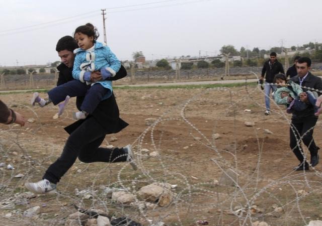 Un grupo de sirios salta por encima la alambrada para huir de la ciudad siria de Ras al-Ain a la ciudad fronteriza turca de Ceylanpinar. 9 de noviembre de 2012. Reuters -
