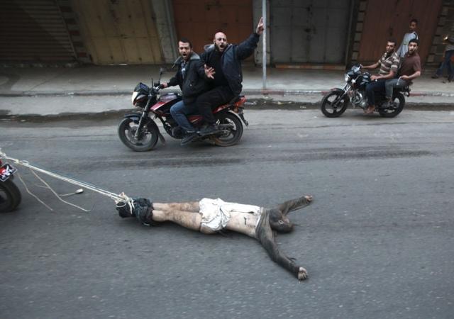 Un grupo de palestinos armados arrastran en motocicleta el cuerpo de un hombre, sospechoso de trabajar para Israel. Gaza 20 de noviembre de 2012. Reuters -