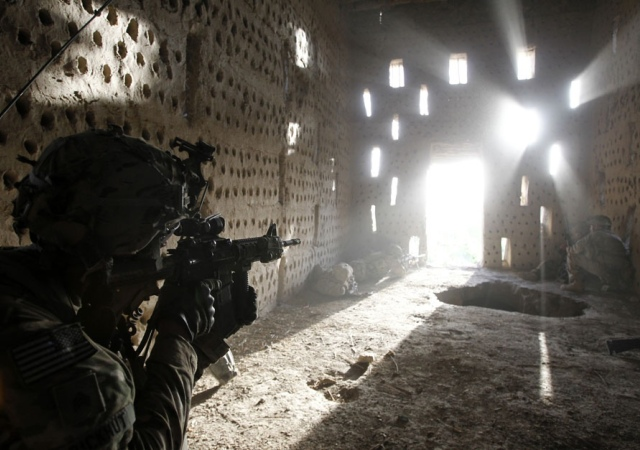 Un soldado de EE.UU. asoma su rifle por una puerta tras ser atacado por los talibanes mientras patrullaba en Zharay distrito en la provincia de Kandahar. Afganistán, 26 de abril 2012. Reuters -