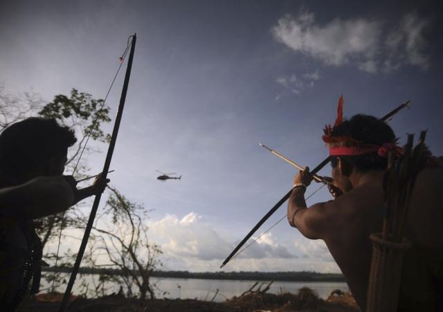 Un grupo de indigenas dispara flechas contra un helicoptero de la policía que sobrevuela la zona de Altamira en el norte de Brasil. 15 de junio de 2012. Reuters -