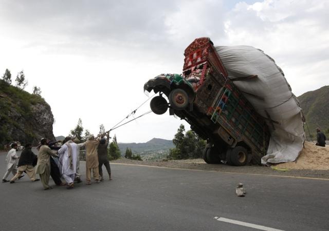 Un grupo de hombres utilizan cuerdas para tratar de enderezar un camión sobrecargado de paja de trigo, que se utiliza como alimento para animales. Pakistán, 13 de abril de 2012. Reuters -