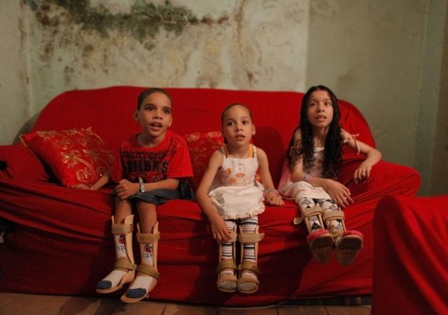 Imagen de tres niños que viven en una de  favela en Brasil con una enfermedad nerviosa que afecta a su coordinación. Brasil 23 de marzo de 2012. Reuters -