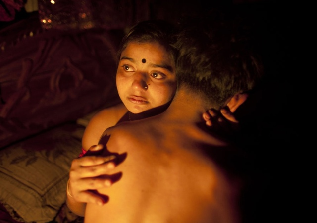 Hashi, una prostituta de 17 años abraza a Babu, su marido,  dentro de su pequeña habitación dl burdel Kandapara en Tangail, Bangladesh. 4 de marzo de 2012 -