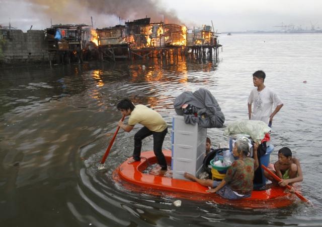 Los residentes de un barrio de Manila reman en un bote improvisado mientras ven como el fuego engulle sus casas. Manila, 11 de mayo 2012. Reuters -