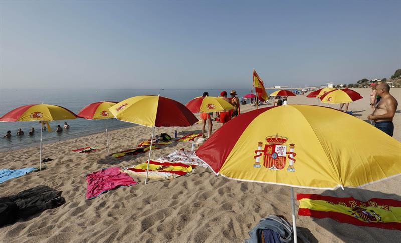 Plantan 12 sombrillas playa con colores bandera de España en playa sombrillas de 3f2137